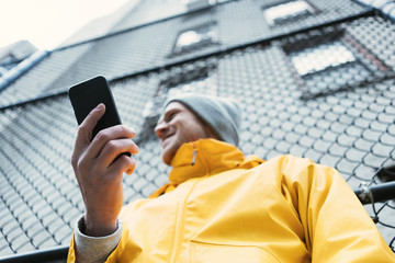 Young man in yellow raincoat standing on the street with mobile phone in hand and smiling