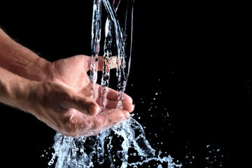 fresh water splashes into human hands against a black background, concept for the protection of water resources, copy space, selected focus