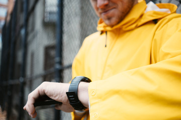 Man in yellow raincoat standing on the street with mobile phone and watching time on smartwatch