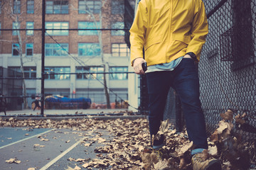 Man in yellow coat walking on the city street with fallen leaves