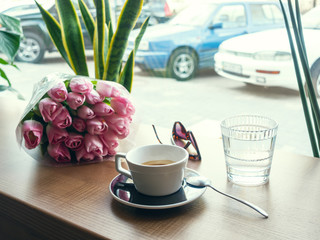 Coffee and spring flowers on coffee shop. Good mood concept.