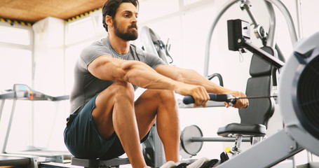 Fit man training on row machine in gym