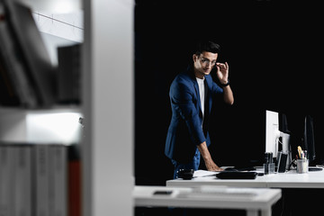 Stylish professional architect in glasses dressed in a blue checkered jacket stands next to the desk with computer in the office