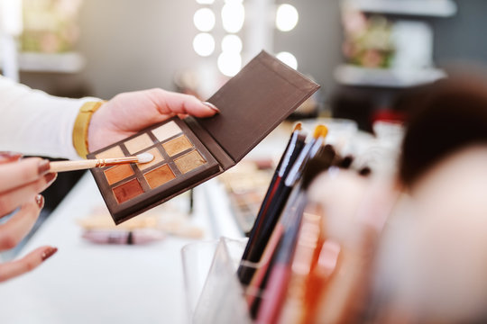 Close up of makeup artist with palette of eyeshadow and brush. Makeup salon interior.
