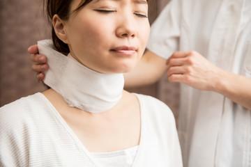 首に包帯を巻く女性