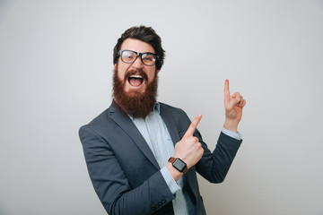 Portrait of excited bearded man in formlwear pointing fingers up over gray background