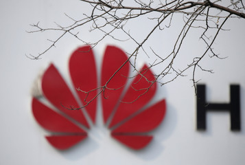 A Huawei company logo is seen behind tree branches in Beijing