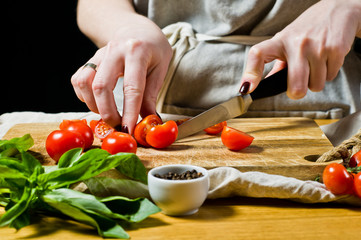 The chef cuts cherry tomatoes on a wooden chopping Board. Black background, side view, space for text