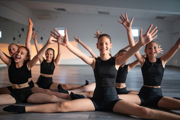 Group of fit happy children exercising ballet and dancing in studio together