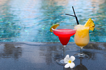 Strawberry daiquiri and pina colada on the pool background. Tropical holidays