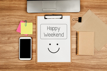 Happy Weekend text on white sheet and office supplies on wooden table