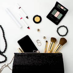 Fashionable female accessories brushes smartphone lipstick eyeshadow and black bag.