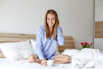 Beautiful blonde model posing in bed wth coffee.