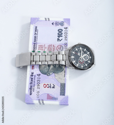 Picture of wrist watch with new 100 rupees note  Isolated on