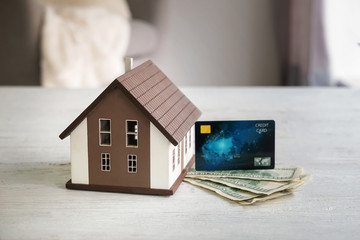 Money, credit card and figure of house on table. Concept of buying property