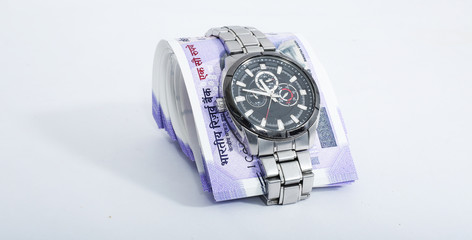 Picture of watch with new 100 rupees notes. Isolated on the white background.