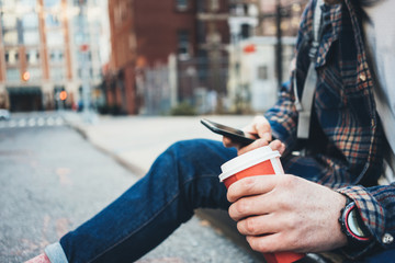 Man sitting on the street resting with cup of hot coffee and using mobile phone. Close-up
