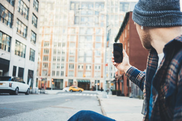 Casual man taking photo on the city street using mobile phone camera