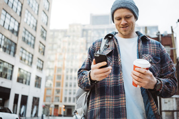 Handsome man walking on the urban street sidewalk with cup of hot coffee and texting on mobile phone. Close-up