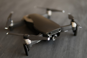 Wall Mural - The concept of using drones in life and industry. Close up Top view Remote control and smartphone macro Details. Copy space. Innovation photography concept. Mate color. A new black drone on a black