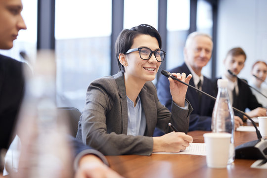Portrait of smiling businesswoman speaking to microphone during press conference or training seminar, copy space