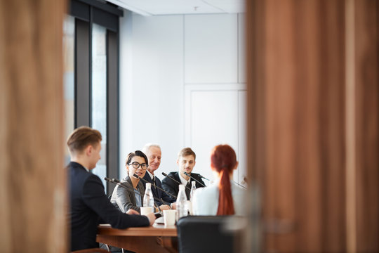 View of business meeting in conference room through open door, copy space