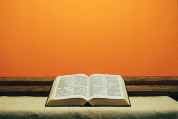 Open Bible on a old table. Beautiful yellow wall background. Religion concept.