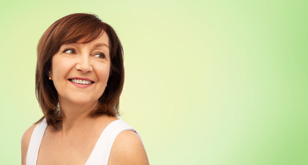 beauty and old people concept - portrait of smiling senior woman over lime green natural background