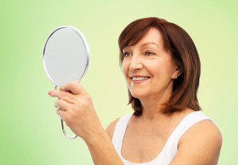 beauty and old people concept - portrait of smiling senior woman with mirror over lime green natural background