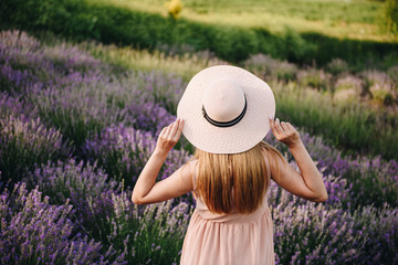 Pregnant girl blonde in a beige dress and straw hat. Lavender field. In anticipation of a child. The idea of a photo shoot. Walk at sunset. Future mom.