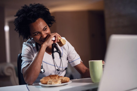 Smiling black female doctor using laptop and eating on a break at her desk.