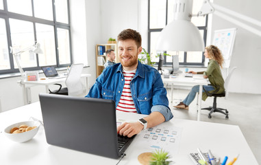 business, technology and people concept - happy smiling creative man with laptop computer working on user interface design at office