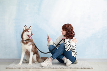 Young woman taking photo of her cute dog near color wall