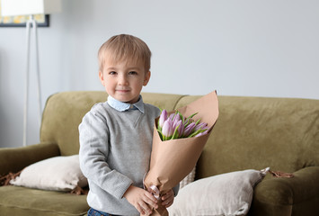 Little boy with flowers for his mother at home. 8 March celebration