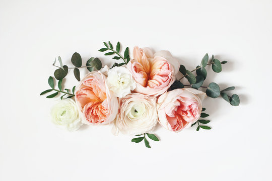 Floral arrangement, web banner with pink English roses, ranunculus, carnation flowers and green leaves on white table background. Flat lay, top view. Wedding or birthday styled stock photography.