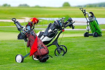 Golf niblick and putter in bags on the golf course with green grass field at summer - luxury recreation hobby for the high society