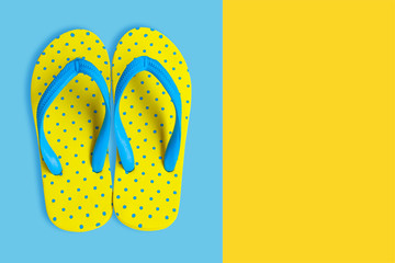 Yellow sandals on yellow and blue color background, flat lay photo