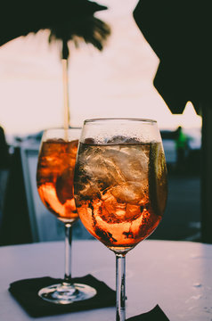 Close up of two glasses of Spritz Veneziano standing on an outdoor table at sunset at Camps Bay in Cape Town, South Africa