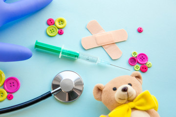 Children vaccination concept. Syringe surrounded with different medical tools and children toys, blue background, flat lay view.