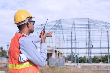 engineer holding radio and ordering at construction working site
