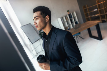 Young concentrated latino man stand in room and look at window. He wear black suit. Guy hold take-away cup. Calm and peaceful