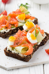 Salmon toast with cream cheese, cucumber and egg. Delicious lunch, healthy food, fish sandwich, diet snack