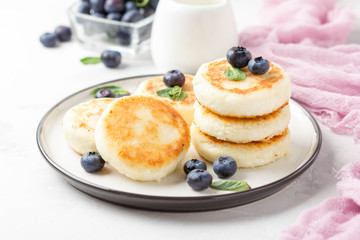 Cheesecakes from cottage cheese, delicious Breakfast, traditional Russian sweet pancakes. With blueberry, mint and sauce