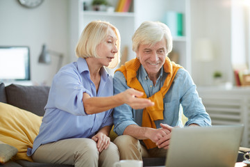 Portrait of contemporary senior couple using laptop together at home and smiling happily, copy space