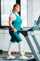 focused overweight girl workouting on treadmill in gym