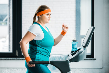 attractive overweight girl workouting on treadmill in gym