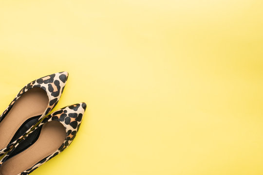 Trendy leopard print shoes on pastel yellow background, minimalistic summer fashion concept. Top view, selective focus