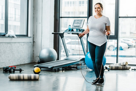 cheerful plus size woman standing with jumping rope in gym