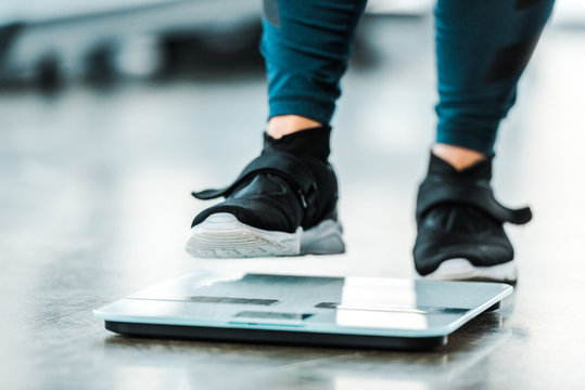 cropped view of plus size woman standing on scales