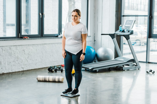 sad overweight woman standing on scales in gym